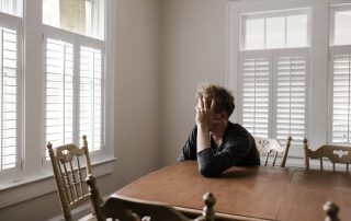 Depressed man sitting at a wooden kitchen table looking out of a window with his head leanig on his hand.